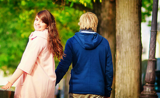 girl with smile holding hands with guy looking back