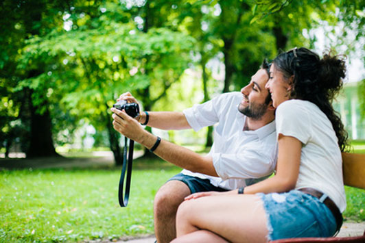couple taking picture outdoors on park bench