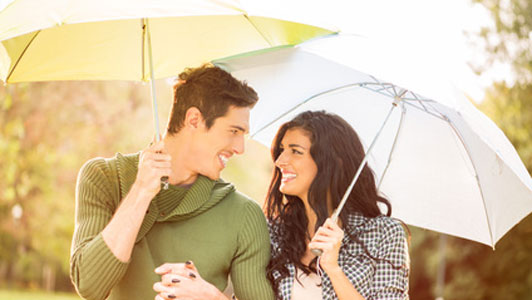 man holding umbrella over woman with umbrella