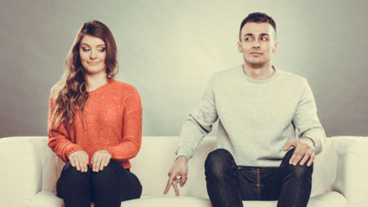 Shy woman and man sitting on sofa