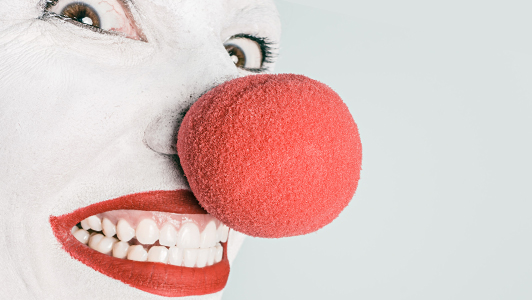 Clown with huge red nose grinning