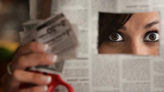 afraid girl hiding behind newspaper