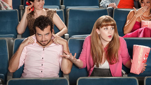 couple in movie theatre man not listening woman frustrated