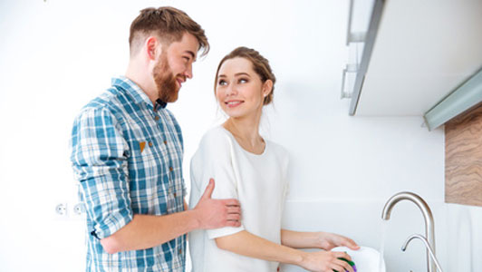 man standing behind woman doing dishes