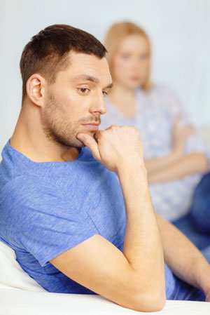 man on couch with woman in background