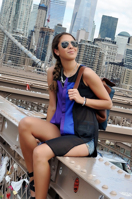 Girl wearng sunglasses and shorts holding a backpack while sitting outside.