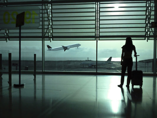 woman with baggage overseeing plane taking off