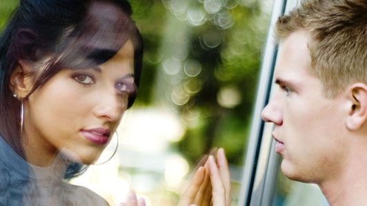 man and women looking at each other through glass