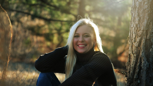 Blonde girl in black sweater sitting in the woods.