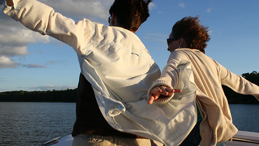 A couple in white jackets holding their arms spread while on a boat.