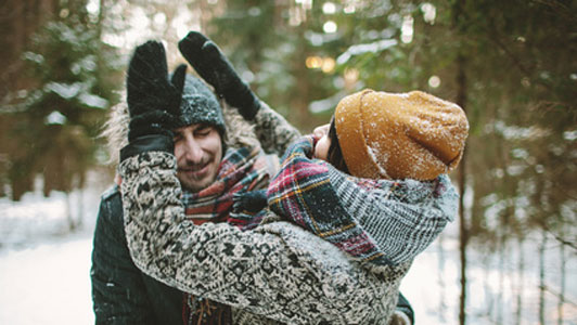 young couple having fun with snow