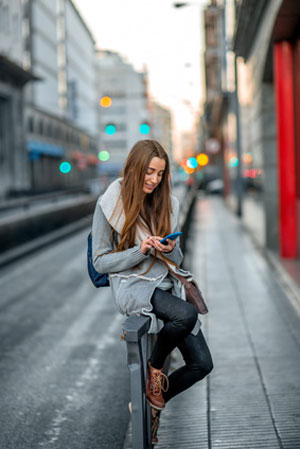 young woman sitting on rail texting