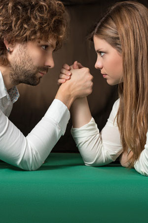 woman faces man in arm wrestling match
