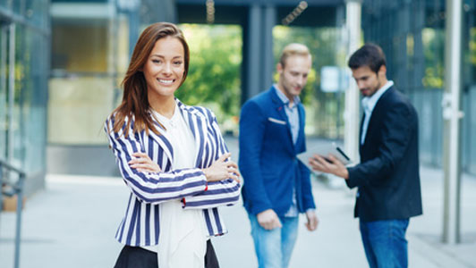 dressed up office woman standing in front of two guys talking