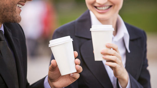two people holding coffee cups smiling