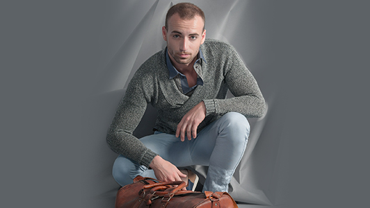 Guy in a gray sweater with a brown bag in front of him.