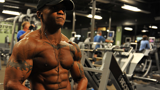 Muscular tattooed guy in a gym wearing a black hat on his head.
