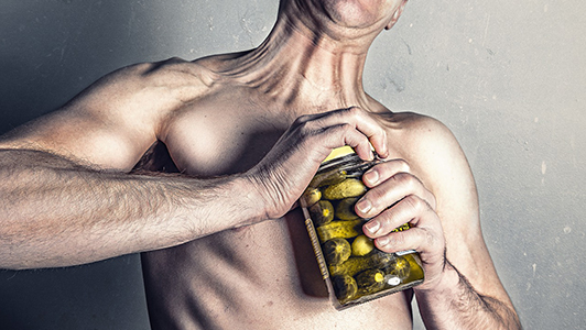 A guy having hard time opening a jar of pickles