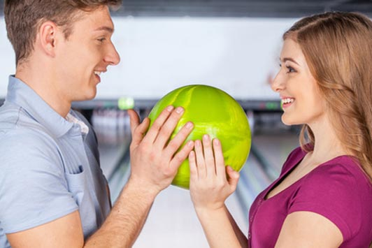 man and woman holding bowling ball on date