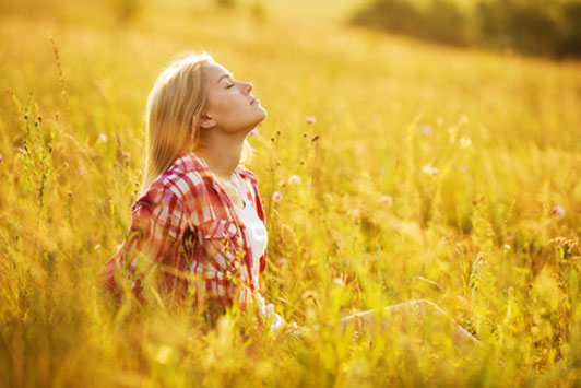 girl in open field taking deep breaths