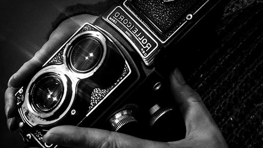 Hands hoding a vintage camera.