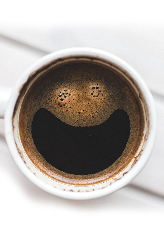 A smiley face in a cup of cofee