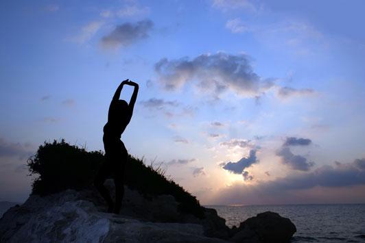 girl stretching overlooking ocean