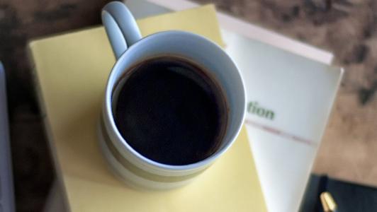A coffee mug over an agenda.