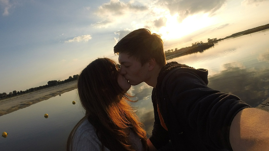 Couple taking a selfie white kissing.