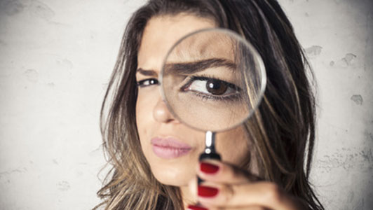 woman holding magnifying glass over eye