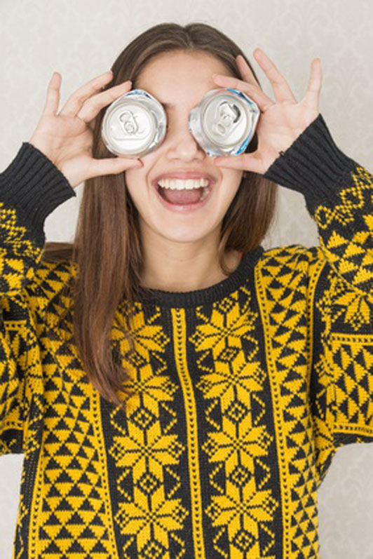 positive girl wearing yellow christmas sweater with aluminum cans over eyes