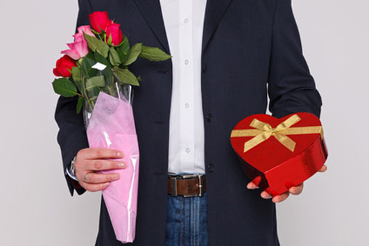 guy holding flowers and heart shaped box of chocolates
