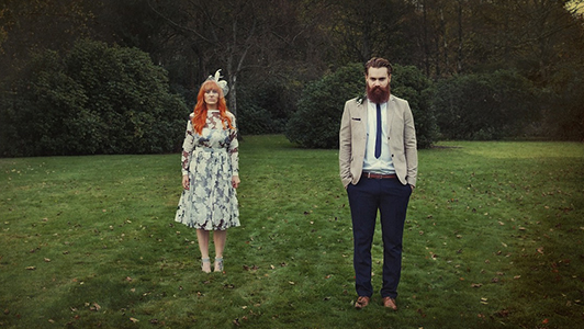 A hipster looking couple standing in the meadow,