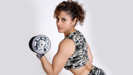 Girl in military cropped top lifting a weight