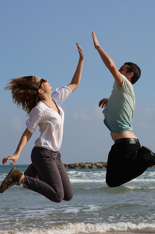 Guy and a girl jumping in the air and giving each other a high five.