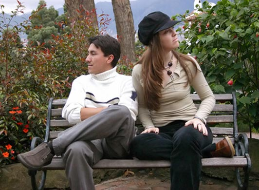 guy and girl sitting together on bench ignoring each other