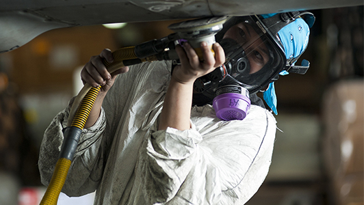 Girl with a mask and white protection suite using a tool.