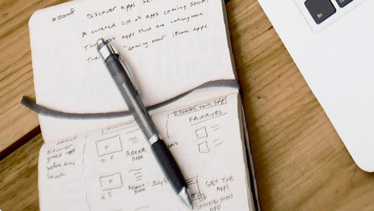 A pen and a notebook with notes.