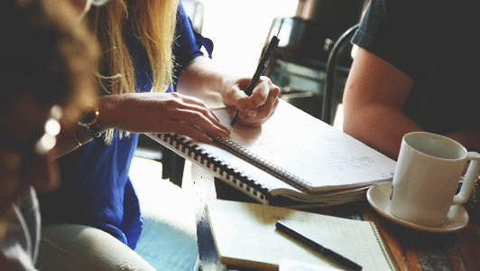A woman writing something doen in her notebook.