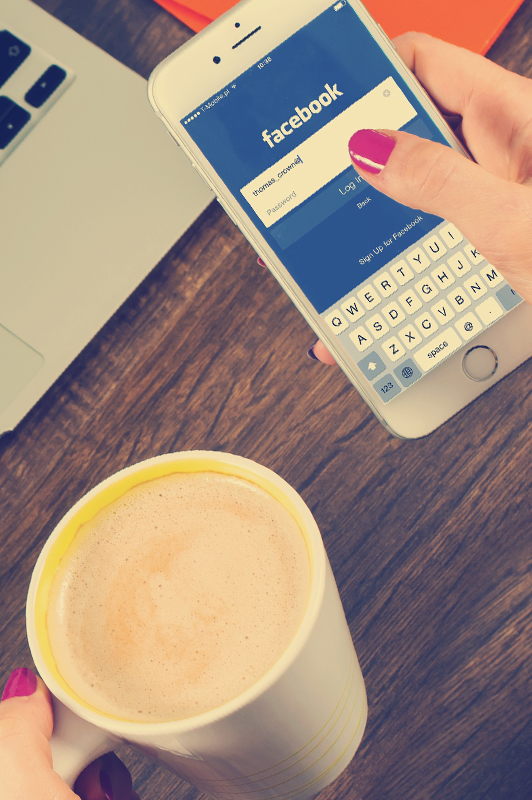 Girl logging in to facebook while holding a cup of coffee.