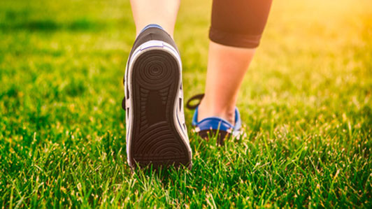 exercise woman stepping through green grass