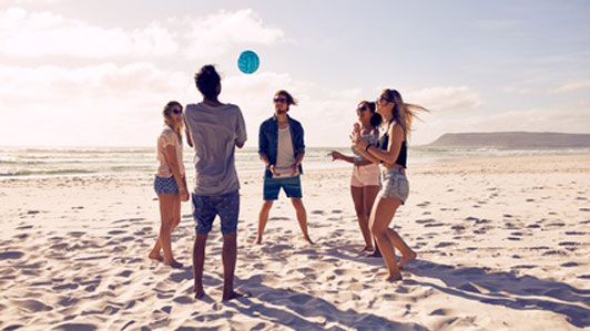 group of friends playing beach ball in a circle