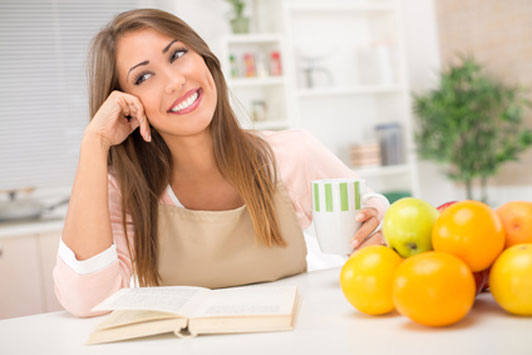 woman holding cup thinking on table with fruit in front of book