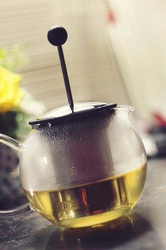 Glass tea pot with steaming tea.