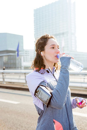 woman out jogging drinking bottled water