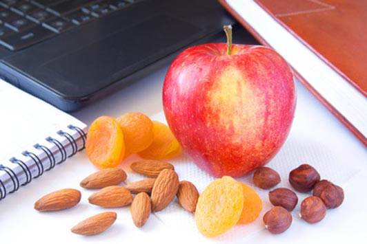 apple nuts and dried fruit on desk