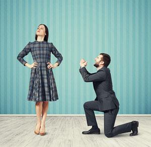 man on knees asking stubborn woman