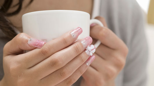 women with nails done holding coffee cup