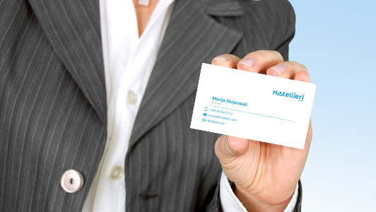 Close up of a woman holding a business card.