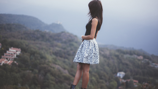 Girl wearing a black top and a white printed skirt
